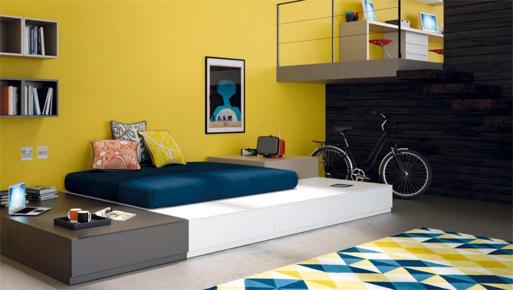 Dormitorio Juvenil con colores neutros, el toque de color lo aporta la pared amarilla y la alfombra.